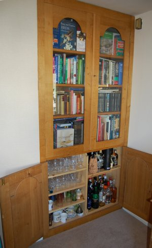 Closed glass dors to the bookshelves, drinks cabinet below.